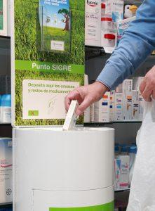 Depositando un envase en el Punto SIGRE de la farmacia